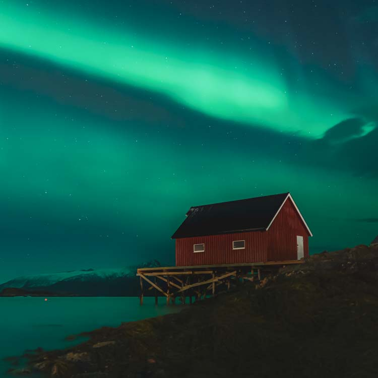 Fishermans cabin under Northern lights at Sommarøy Tromsø Norway